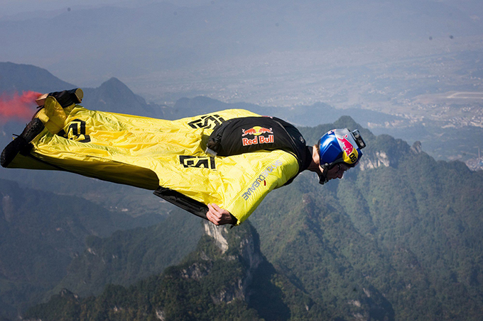 Contest of flying people held in China Wingsuit flying is the sport of flying through the air using a special jumpsuit, called a wingsuit, which adds surface area to the human body to enable the wearer to  fly . The contest on Tianmen Mountain was the first of its kind and featured 15 athletes wearing wingsuits jumping off a cliff and then completing a 1.2-km-long obstacle course while flying, according to the World Wingsuit League, one of the organizers of the contest, chinadaily.com.cn reports
