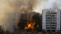A raging wildfire ripped through parts of Israel s third-largest city on Thursday, forcing tens of thousands of people to evacuate their homes and prompting a rare call-up of hundreds of military reservists to join overstretched police and firefighters. Spreading quickly due to dry, windy weather, the fire quickly spread through Haifa s northern neighborhoods. While there were no serious injuries, several dozen people were hospitalized for smoke inhalation.