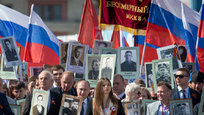 Russian President Vladimir Putin joined a vast crowd of people marching, holding a banner reading  Immortal Regiment  and portraits of relatives who fought in World War II through Red Square, in Moscow, Russia, Saturday, May 9, 2015. The march of the so-called Immortal Regiment is part of Saturday's commemoration of the 70th anniversary of victory over Nazi Germany. Putin took a photograph of his father in his naval uniform